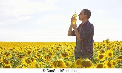 Man farmer hand hold bottle of sunflower oil lifestyle the...
