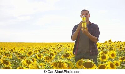 Man farmer hand hold bottle of sunflower oil n the field at...