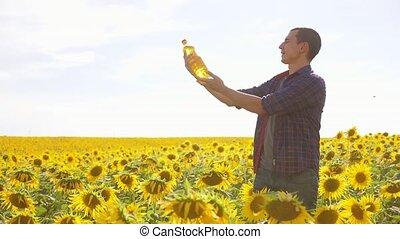 Man farmer hand hold bottle of sunflower oil n the field at...