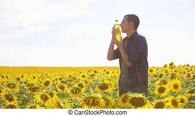 Man farmer hand hold bottle of sunflower oil n the field...