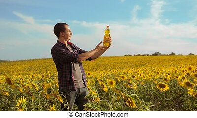 Man farmer hand hold bottle of sunflower oil the field at...