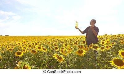 Man farmer hand hold lifestyle bottle of sunflower oil the...