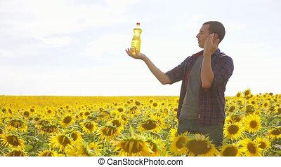 Man farmer hand hold lifestyle bottle of sunflower oil the...
