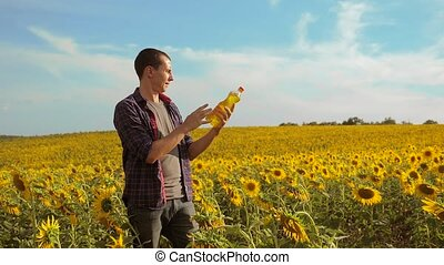 Man farmer hand lifestyle hold bottle of sunflower oil the...