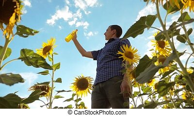 man farmer holding in hand a plastic bottle sunflower...