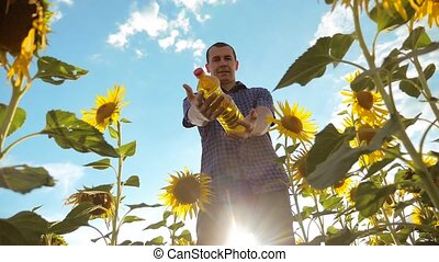 man farmer holding in hand a plastic bottle sunflower oil...