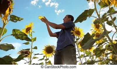 man farmer holding in hand a plastic bottle sunflower oil...