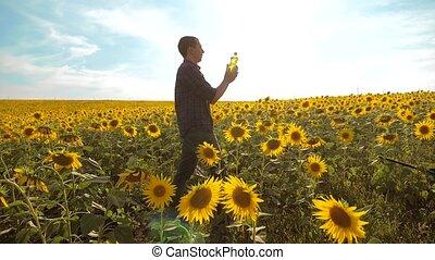 Man farmer lifestyle hand hold bottle of sunflower oil the...