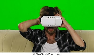 Man fascinated by the movie in VR the mask. Green screen