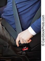 Man fastening his seatbelt in a car