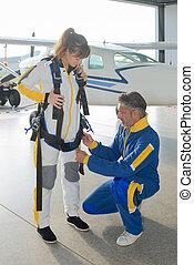 Man fastening straps on parachutist's harness