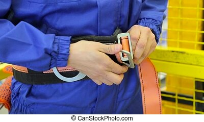 man fastens a safety belt in warehouse