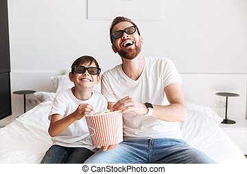 Man father dad with his son watching TV eating pop corn wearing 3D glasses.