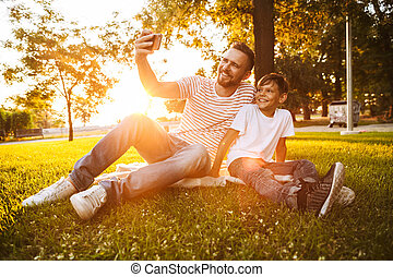 Man father have a rest with his son outdoors in park make selfie by mobile phone.
