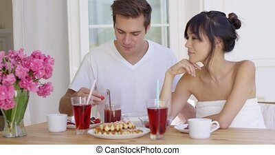 Man feeding his wife fruit at breakfast - Smiling man...