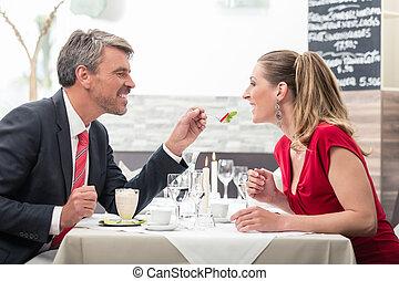 Man feeding his wife in restaurant