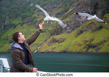 Man feeding seagulls flying over the ferry boat
