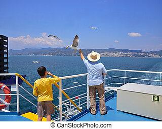 Man feeding seagulls in flight on ferry deck.