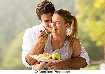 man feeding wife breakfast