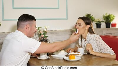 young man feeds smiling girlfriend with tasty berry cake having date at wooden table in confectionery shop