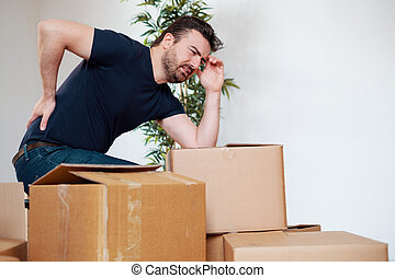 Man feeling back ache cramp moving heavy boxes