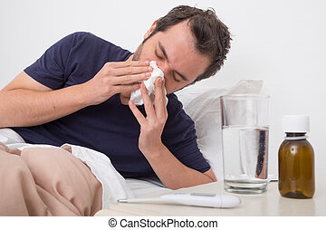 Man feeling bad lying in the bed and blowing his nose
