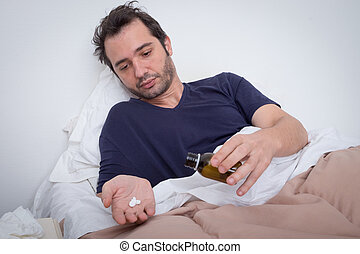 Man feeling bad lying in the bed and taking pills