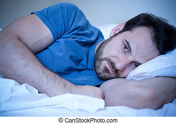 Man feeling sick and sad at night lying in his bed