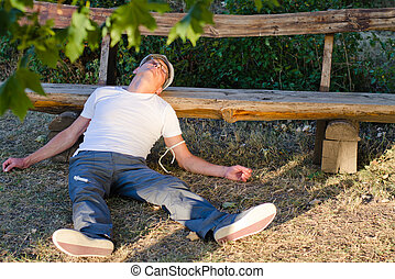 Caucasian middle-aged man lying down on the ground leaning his head on a bench feeling sick