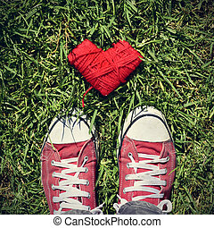 man feet and heart-shaped coil of red cord on the grass, ...