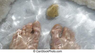 Man feet in pure salt water of Dead Sea, Israel - Close-up...