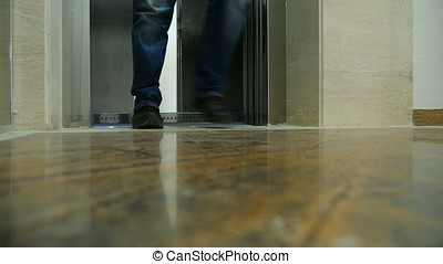 Man feet leaving the elevator. Unrecognisable person