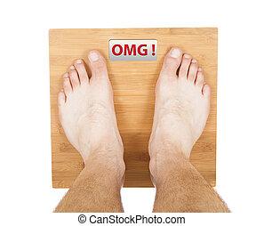 man feet on the scale. OMG word on display