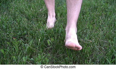 Man feet run by in grass slow motion