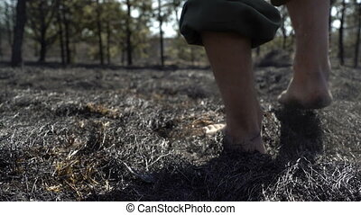 Man feet walking barefoot by burned grass after big forest wildfire, ecological disaster, nature destruction, concept sorrow