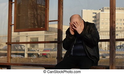 Man felt headache and sudden giddiness at bus stop on city street. Dull ache in people occurs suddenly.