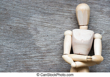 Man figure posing in fold one's arms over the chest on wooden background with copy space (Concept for business thinking, planning)