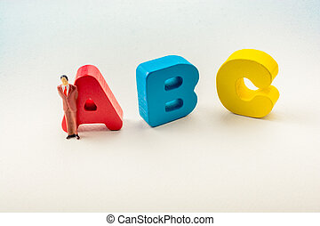 Man figurine and Letters of abc on white