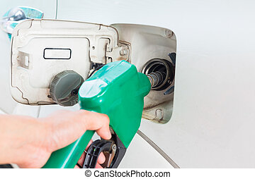 Man fill up fuel at a gas station.