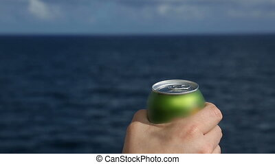 man filled soda into a glass on the ocean