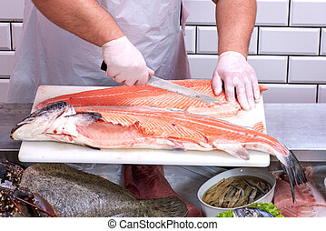 Man filleting a salmon in fish store