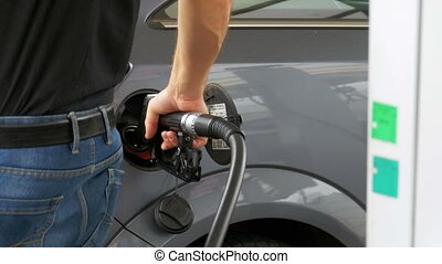 Man filling car with Diesel Fuel. Man's hand using a petrol pump to fill his car up with fuel.