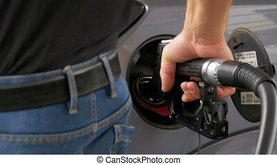 Man filling car with Diesel Fuel. Man's hand using a petrol...