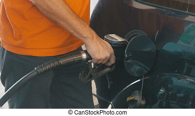 Man filling car with gas. Man's hand using a petrol pump to...