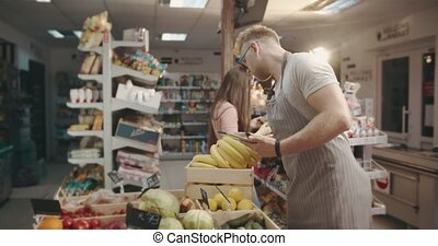 Man filling database on tablet about fresh organic fruits - ...