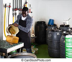 Man filling glass jars with pickled olives