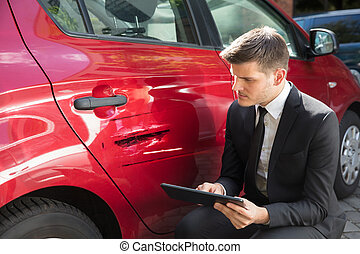 Man Filling Insurance Form Near Damaged Car