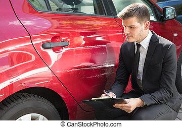 Man Filling Insurance Form Near Damaged Car