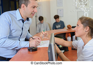 Man filling out form at reception