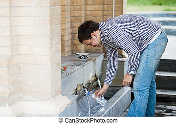 Man fills a bottle of mineral water from spring source